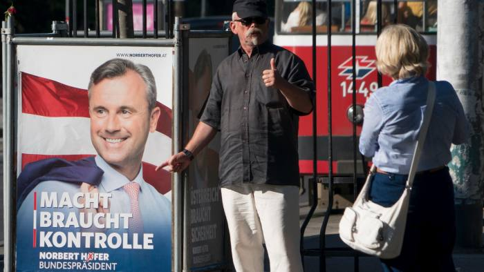A man gives thumbs up in front of an election campaign poster of the presidential candidate Norbert Hofer from the far-right Freedom Party (FPOe) in Vienna, on August 31, 2016. Austria will re-run its presidential election on October 2. / AFP / JOE KLAMAR (Photo credit should read JOE KLAMAR/AFP/Getty Images)