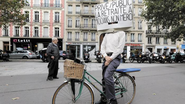 """A man on his bicycle attends a demonstration over pension reforms in Paris...A man on his bicycle attends a demonstration over pension reforms in Paris, September 10, 2013. French unions take to the streets on Tuesday in protest against a reform of the country's indebted pension system, with some disruption in transport expected but no mass upheaval against an overhaul seen as moderate in scope. The placard reads """"Private and public sector workers, retirement at hundred, no thank you ! """". REUTERS/Jacky Naegelen (FRANCE - Tags: POLITICS BUSINESS EMPLOYMENT SOCIETY) - RTX13FS1"""