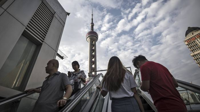 Pedestrians ride an escalator near the Oriental Pearl Tower in the Lujiazui Financial District in Shanghai, China, on Monday, Sept. 4, 2017. The Chinese central bank's tight leash on liquidity is straining the bond market, with the benchmark sovereign yield climbing to near the highest level since April 2015. Photographer: Qilai Shen/Bloomberg