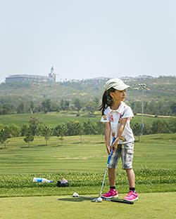 Summer camp student Yuan Jinqing, six, takes aim