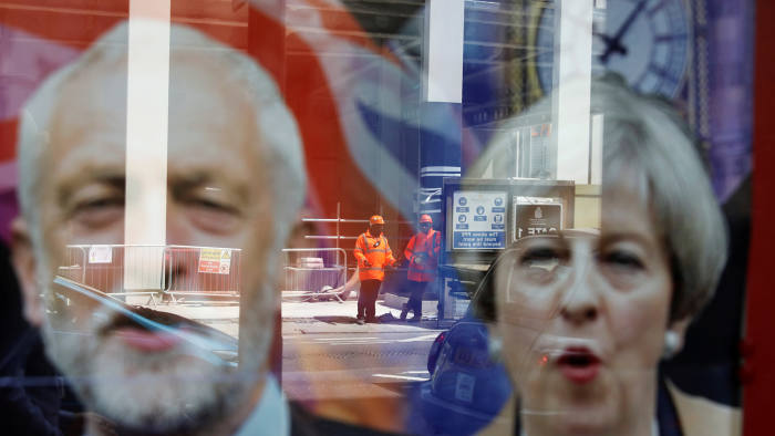 Workers in protective equipment are reflected in the window of a betting shop with a display inviting customers to place bets on tbe result of the general election with images of Britain's Prime Minister Theresa May and opposition Labour Party leader Jeremy Corbyn, in London, June 7, 2017. REUTERS/Marko Djurica TPX IMAGES OF THE DAY