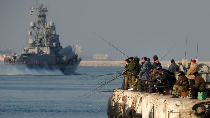 A Russian naval ship passes fishermen in Sevastopol bay on Wednesday