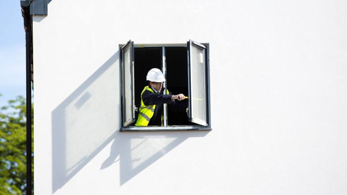 A workman inspects a window fitting at a Persimmon Plc construction site in Uxbridge, U.K., on Monday, Aug. 17, 2015. Persimmon Plc, the U.K.'s second biggest homebuilder by market value, is training former soldiers amid a shortage of bricklayers. Photographer: Jason Alden/Bloomberg