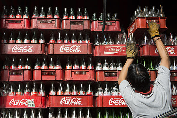 A worker loads a delivery truck with empty Coca-Cola bottles in Mexico City, Mexico, on Thursday, Sept. 5, 2013