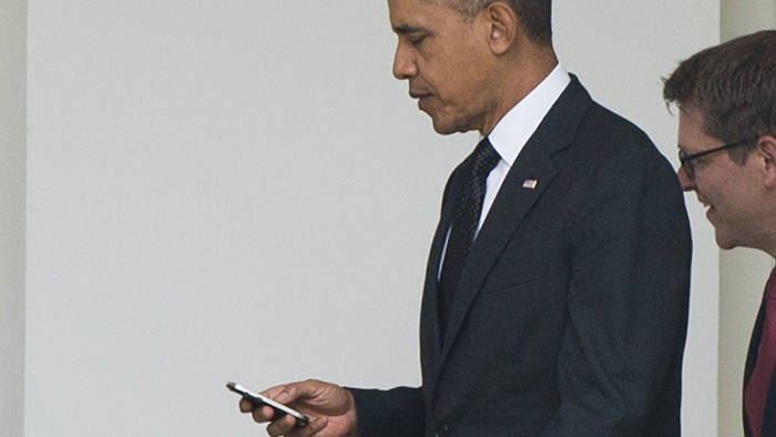 US President Barack Obama uses a cellphone as he walks to the West Wing of the White House