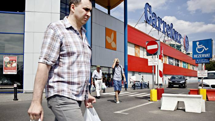 "Men walk out of a Carrefour store after shopping, on July 9, 2013, in Bucharest, Romania. With 119 stores and sales of local one billion euros in 2011, the retail giant Carrefour intends to use the discovery by Romanians ""joys"" of consumption, after decades of deprivation under the communist regime. AFP PHOTO / ANDREI PUNGOVSCHI (Photo credit should read ANDREI PUNGOVSCHI/AFP/Getty Images)"
