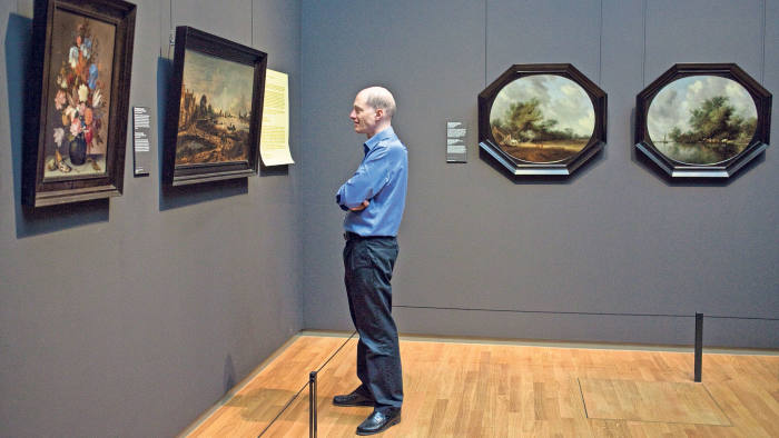 Alain de Botton reads his sign beside Aert van der Neer's 'River View by Moonlight' (1645) at the 'Art is Therapy' exhibition