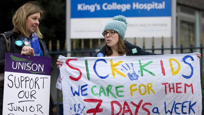 Demonstrators hold placards in support of a 24-hour strike by junior doctors over pay and conditions outside King's College Hospital in London on February 10, 2016. Thousands of junior doctors began a second strike at English hospitals on Wednesday against proposed new working conditions and pay rates. Junior doctors -- all medics below consultant level -- were providing emergency care only from 8:00am (0800 GMT) in the 24-hour strike. / AFP / JUSTIN TALLIS (Photo credit should read JUSTIN TALLIS/AFP/Getty Images)