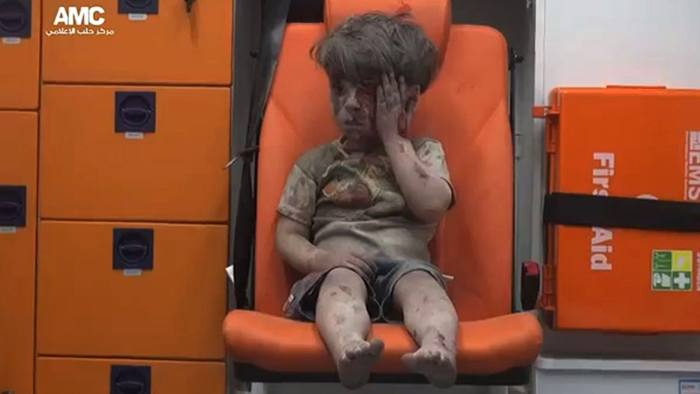 """An image grab taken from a video uploaded by the Syrian opposition's activist group Aleppo Media Centre (AMC) on August 17, 2016 is said to show a young Syrian boy covered in dust and blood touching a wound on his head as he sits in shock in an ambulance after being rescued from the rubble of a building hit by an air strike in the rebel-held Qaterji neighbourhood of the northern Syrian city of Aleppo. / AFP PHOTO / AMC / HO / === RESTRICTED TO EDITORIAL USE - MANDATORY CREDIT """"AFP PHOTO / HO / AMC """" - NO MARKETING NO ADVERTISING CAMPAIGNS - DISTRIBUTED AS A SERVICE TO CLIENTS FROM ALTERNATIVE SOURCES, AFP IS NOT RESPONSIBLE FOR ANY DIGITAL ALTERATIONS TO THE PICTURE'S EDITORIAL CONTENT, DATE AND LOCATION WHICH CANNOT BE INDEPENDENTLY VERIFIED === / HO/AFP/Getty Images"""