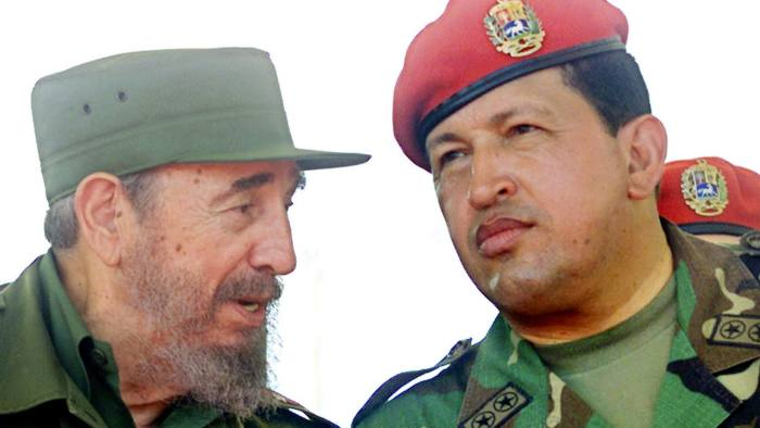 FILE PHOTO OF FORMER VENEZUELAN PRESIDENT CHAVEZ WITH CUBAN COUNTERPART CASTRO...Former Venezuelan President, Hugo Chavez, chats with Cuban President Fidel Castro on Venezuela's Margarita Island, in this file photo taken on December 11, 2001. Military officers forced Chavez out after the leftist former paratrooper faced months of mounting opposition that broke out in street violence that left 15 dead on April 11, 2002. REUTERS/Jose Miguel Gomez/File