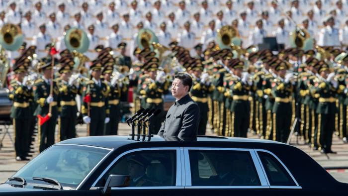 Chinese president and leader of the Communist Party Xi Jinping rides in an open top car in front of Tiananmen Square and the Forbidden City during a military parade on September 3 2015 in Beijing, China