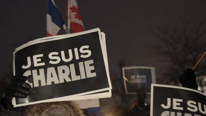 """People holds signs reading """"I  Am Charlie"""" during a vigil January 7, 2015 outside  City Hall in Montreal, Canada  for the victims of the shooting at the office of the French satirical magazine Charlie Hebdo.  Twelve people were killed when several gunmen opened fire at Charlie Hebdo's headquarters in Paris, France on January 7th. AFP PHOTO / MARC BRAIBANTMarc Braibant/AFP/Getty Images"""