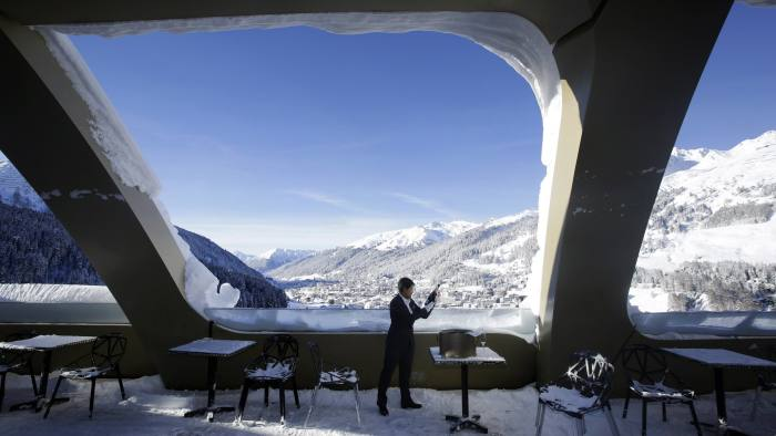 A hotel employee checks a bottle of champagne as he stands on the snow covered bar terrace of the InterContinental Hotel Davos, operated by InterContinental Hotels Group Plc (IHG), in this arranged photograph taken ahead of the World Economic Forum (WEF) in Davos, Switzerland, on Monday, Jan. 18, 2016. World leaders, influential executives, bankers and policy makers attend the 46th annual meeting of the World Economic Forum in Davos from Jan. 20 - 23. Photographer: Matthew Lloyd/Bloomberg