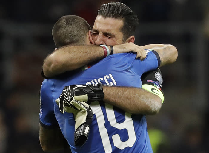 Italy goalkeeper Gianluigi Buffon is hugged by teammate Leonardo Bonucci after their team was eliminated in the World Cup qualifying play-off second leg soccer match between Italy and Sweden, at the Milan San Siro stadium, Italy, Monday, Nov. 13, 2017. (AP Photo/Luca Bruno)