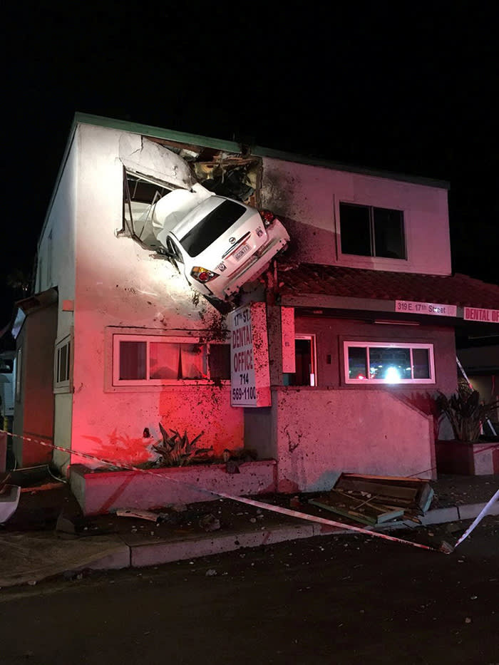 A car dangles off the second floor of a building after speeding into a median and going airborne, according to local media, in Santa Ana, California, U.S., January 14, 2018, in this picture obtained from social media. OCFA PIO/via REUTERS THIS IMAGE HAS BEEN SUPPLIED BY A THIRD PARTY. MANDATORY CREDIT.NO RESALES. NO ARCHIVES TPX IMAGES OF THE DAY