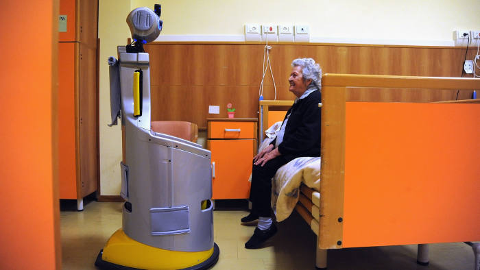 A robot of the project Robot-Era goes to take a lady in the room to accompany her in the dining room at nursing residence San Lorenzo on December 19, 2015 in Florence, Italy
