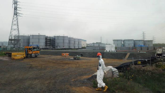 A construction worker walks near water tanks at the Fukushima Dai-ichi nuclear plant on June 12 2013
