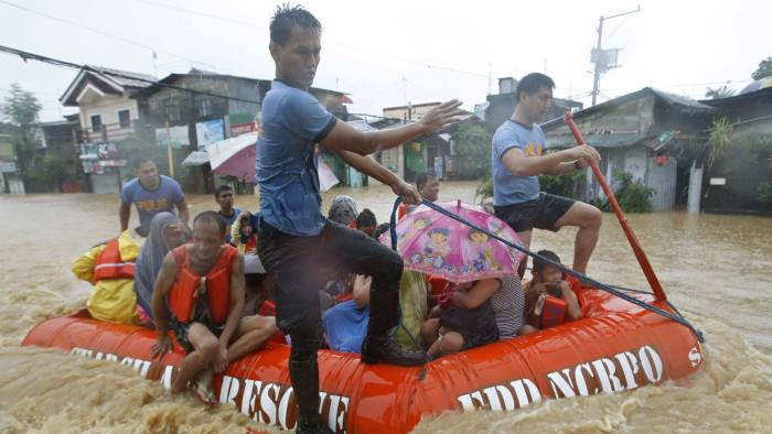 Flood victims are evacuated in a rescue boat after their homes were swamped by heavy flooding in Marikina, Metro Manila...Flood victims are evacuated in a rescue boat after their homes were swamped by heavy flooding in Marikina, Metro Manila September 19, 2014. Heavy rain in the Philippine capital, Manila, caused flooding in many areas on Friday, shutting schools, government offices and financial markets as a tropical storm made landfall to the north. Thousands of residents in low-lying areas were moved to higher ground, officials said, as flood waters rose quickly after the equivalent of half a month's usual rain fell in six hours. REUTERS/Erik De Castro (PHILIPPINES - Tags: DISASTER ENVIRONMENT TPX IMAGES OF THE DAY)