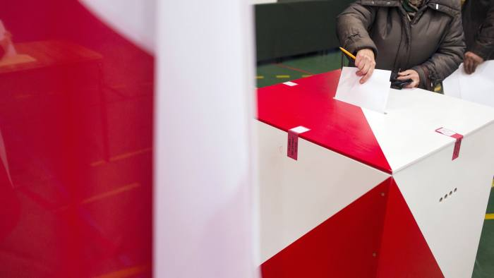 A voter casts his ballot in a ballot box during the Polish general election in Warsaw, Poland, on Sunday, Oct. 25, 2015. Poland's opposition is on the cusp of ending an eight-year rule by Civic Platform with a win in a parliamentary election on Sunday, securing a mandate to take charge of the European Union's biggest eastern economy. Photographer: Bartek Sadowski/Bloomberg