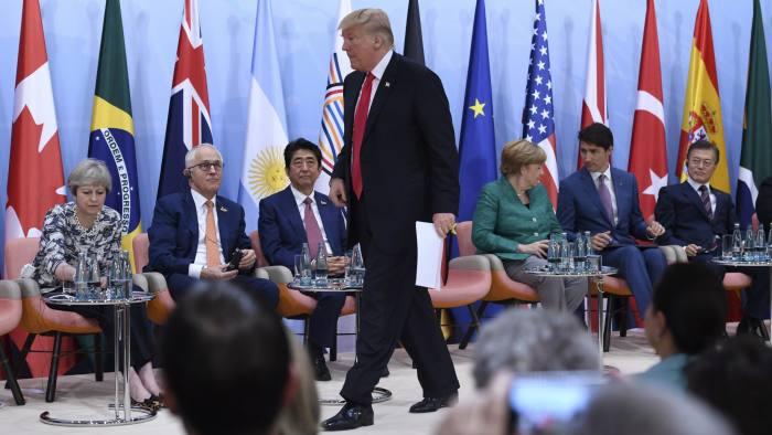 "US President Donald Trump, center, wlks to the desk to deliver a speech during the panel discussion ""Launch Event Women's Entrepreneur Finance Initiative"" on the second day of the G-20 summit in Hamburg, Germany, Saturday, July 8, 2017. (Patrik Stollarz/Pool Photo via AP)"