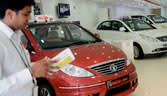 Potential customers look at Indian made Tata cars at a show room in New Delhi