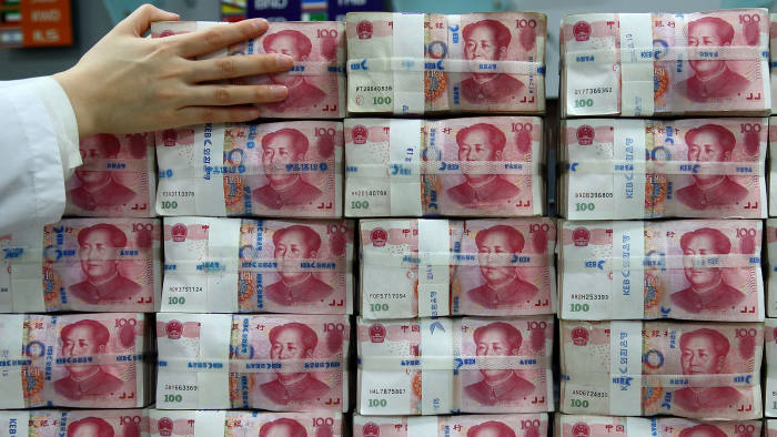 Chinese one-hundred yuan banknotes are stacked for a photograph at the Korea Exchange Bank headquarters in Seoul, South Korea, on Thursday, Feb. 27, 2014
