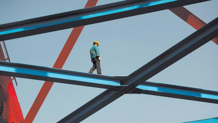 A man walks along a steel beam
