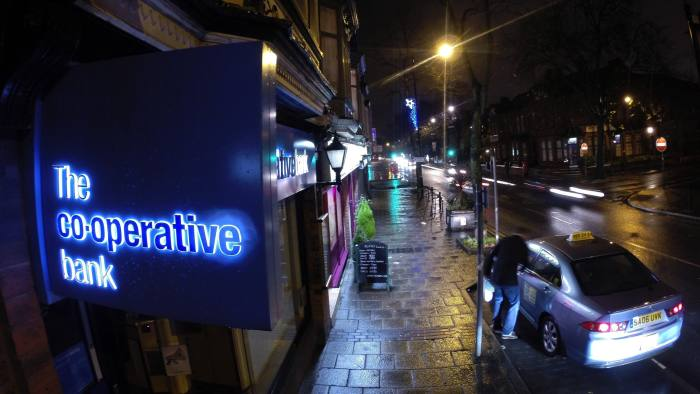 """An illuminated logo sits on a sign outside a Co-Operative Bank Plc branch, a unit of Co-Operative Group Ltd., at night in Manchester, U.K., on Sunday, Dec. 14, 2014. Co-Op Bank Chief Executive Officer Niall Booker earlier this month said it """"would come as no surprise"""" if the bank didn't meet the Bank of England's minimum capital requirements when the results of the stress test are released on Dec. 16, which models how banks would fare in another financial crisis. Photographer: Paul Thomas/Bloomberg"""