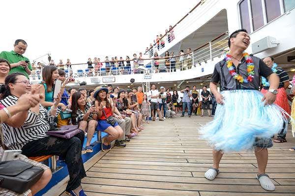 Men perform Hawaiian dancing on the ship's deck as an audience looks on