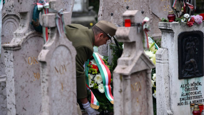 A Hungarian soldier adjusts a ribbon at the grave of victims of the 1956 uprising in the Fiumei street cemetery in Budapest on November 4, 2013 during the anniversary for victims of the Hungarian revolution and freedom fighting against Soviet occupation. Hungary's uprising erupted on October 23, 1956 and was crushed by Soviet tanks on November 4, sealing the country's fate as a satellite state of Moscow until the fall of the Iron Curtain in 1989. AFP PHOTO / ATTILA KISBENEDEK (Photo credit should read ATTILA KISBENEDEK/AFP/Getty Images)