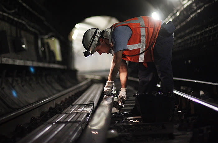 LONDON - NOVEMBER 06: A worker cleans the ceramic insulator pots under the live rail near Pimlico Underground Station on October 6, 2008 in London. A team of four cleaners known as a 'Hoover Gang' willl spend 3-4 hours a night sweeping, Hoovering and clearing the tracks next to the platform and up to 50 meters into the tunnels. The process is repeated every two weeks. (Photo by Peter Macdiarmid/Getty Images)