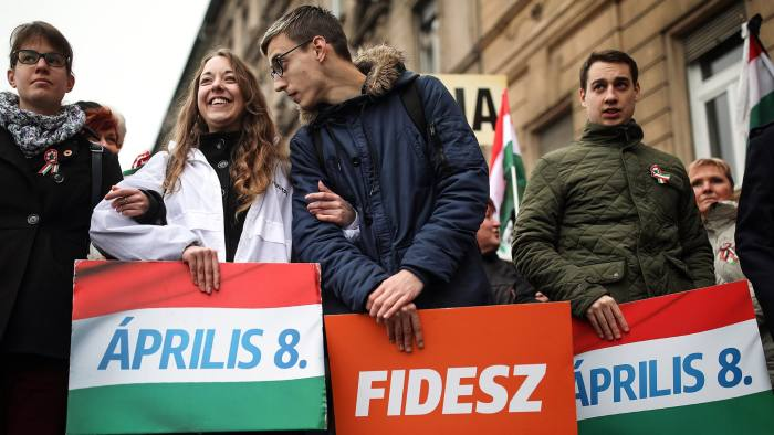Supporters of the Fidesz party hold placards during a peace march in Budapest, Hungary, on Thursday, March 15, 2018. With less than three weeks to go before the April 8 parliamentary vote, Prime Minister Viktor Orban is tipped for a third consecutive term, and most polls measure his Fidesz party's support at roughly equal to the four biggest opposition parties combined. Photographer: Akos Stiller/Bloomberg