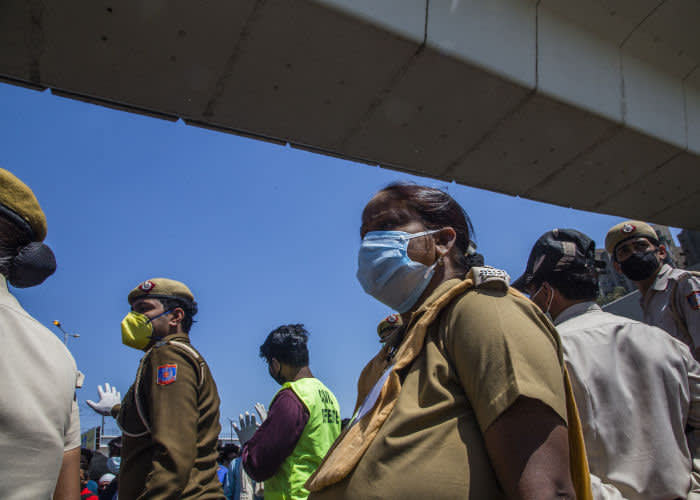 Migrant workers in New Delhi wait to board buses
