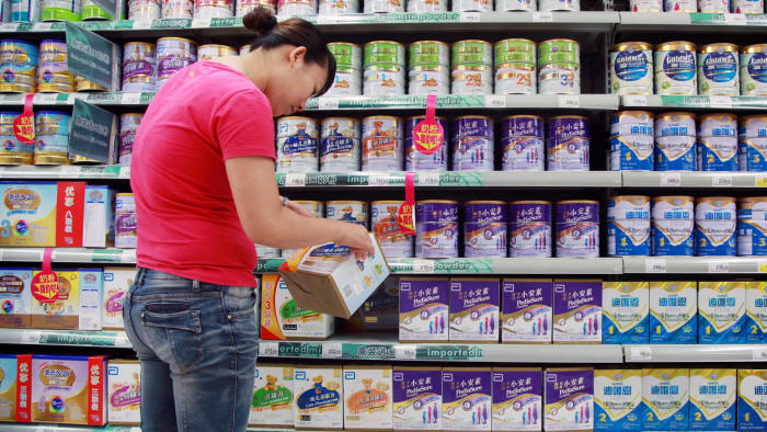 A customer selects baby milk in a supermarket in Haikou, south China's Hainan province on August 7, 2013. China has fined six mostly foreign baby formula companies a total of 108 million USD for price-fixing, the government said on August 7, in reportedly the country's biggest-ever anti-trust penalty. The firms fined were Mead Johnson and Abbott from the US, Dumex, a subsidiary of France's Danone, a China arm of Royal FrieslandCampina of the Netherlands, New Zealand giant Fonterra -- at the centre of a health scare this week -- and China's Biostime, the National Development and Reform Commission (NDRC) said in a statement. CHINA OUT AFP PHOTO (Photo credit should read STR/AFP/Getty Images)