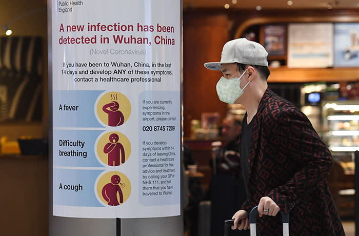 Mandatory Credit: Photo by ANDY RAIN/EPA-EFE/Shutterstock (10537881g) A man wearing a face mask walks past a Coronavirus notice at Heathrow Airport in London, Britain, 24 January 2020. Britain is to begin monitoring direct flights from China to stem the spread of the coronavirus. Britain to begin monitoring direct flights from China to stem the spread of the coronavirus, London, United Kingdom - 24 Jan 2020