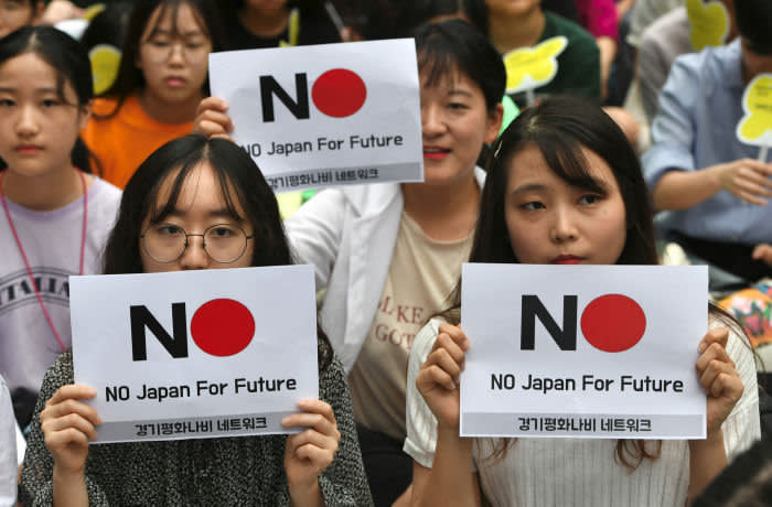 "TOPSHOT - South Korean protesters hold signs during a weekly anti-Japanese demonstration supporting ""comfort women"" who served as sex slaves for Japanese soldiers during World War II, near the Japanese embassy in Seoul on July 24, 2019. - After South Korea's high court ordered Japanese firms that used forced labour to compensate Korean victims, Japan earlier this month restricted the export of several chemicals to South Korea that are crucial to its world-leading chip and smartphone companies. (Photo by Jung Yeon-je / AFP) (Photo credit should read JUNG YEON-JE/AFP/Getty Images)"