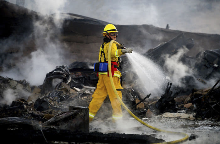 A firefighter sprays water on a leveled home as the Hillside Fire burns in San Bernardino, Calif., on Thursday, Oct. 31, 2019. Whipped by strong wind, the blaze destroyed multiple residences. (AP Photo/Noah Berger)