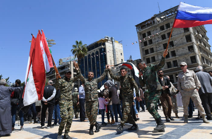 Syrians dressed in Military attire wave the Syrian and Russian flag as they gather in Aleppo's Saadallah al-Jabiri square on April 14, 2018, to condemn the strikes carried out by the United States, Britain and France against the Syrian regime. / AFP PHOTO / George OURFALIAN (Photo credit should read GEORGE OURFALIAN/AFP via Getty Images)