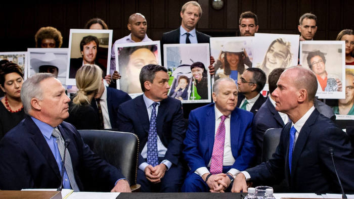 Mandatory Credit: Photo by MICHAEL REYNOLDS/EPA-EFE/Shutterstock (10459619s) President and CEO of Boeing Dennis Muilenburg (R) and Vice President and Chief Engineer of Boeing Commmercial Airplanes John Hamilton (L) sit in front of people holding pictures of their loved ones who died in Boeing crashes, to testify before the US Senate Committee on Commerce, Science and Transportation hearing on 'Aviation Safety and the Future of Boeing's 737 MAX', on Capitol Hill in Washington, DC, USA, 29 October 2019. Boeing 737 MAX aircraft remain grounded following two crashes, Ethiopian Airlines flight 302 and Lion Air flight 610, that killed 346 people. US Senate Committee on Commerce, Science and Transportation hearing on Aviation Safety and the Future of Boeing's 737 MAX, Washington, USA - 29 Oct 2019