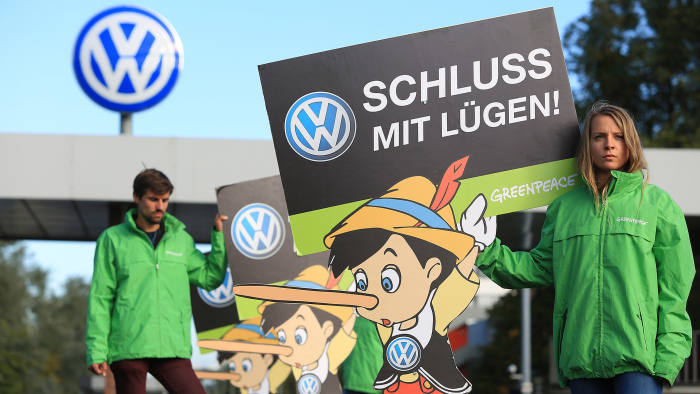 Members of the environmental action group Greenpeace hold up Pinocchio placards during a protest outside the Volkswagen AG headquarters in Wolfsburg, Germany, on Friday, Sept. 25, 2015