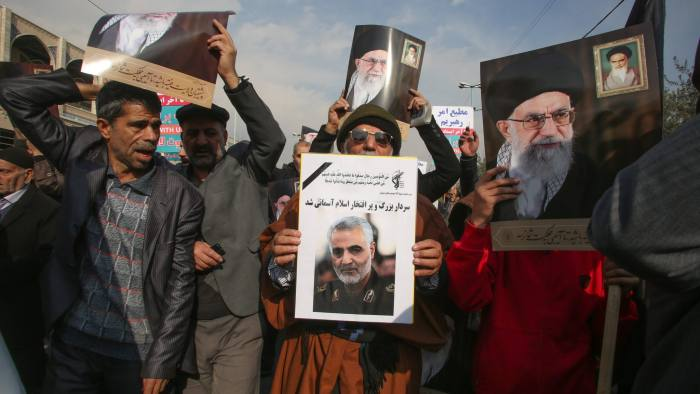 """Iranians holds posters of Iran's supreme leader Ayatollah Ali Khamenai (background) and slain commander Qasem Soleimani during a demonstration in the capital Tehran on January 3, 2020 against the killing of Iranian Revolutionary Guards top commander in a US strike in Baghdad. - Iran warned of """"severe revenge"""" and said arch-enemy the United States bore responsiblity for the consequences after killing one of its top commanders, Qasem Soleimani, in a strike outside Baghdad airport. (Photo by ATTA KENARE / AFP) (Photo by ATTA KENARE/AFP via Getty Images)"""