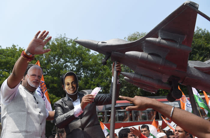 India's Congress party workers wear masks of Indian Prime Minister Narendra Modi (L) and business tycoon Anil Ambani, as they pose in front of a model of a Rafale fighter jet during a protest against the Rafale fighter jet deal, in Mumbai on September 27, 2018. - Former French president Francois Hollande has fuelled controversy over India's multi-billion-dollar 2016 purchase of 36 Rafale fighter jets, saying that France was given no choice on the Indian partner for manufacturer Dassault. (Photo by INDRANIL MUKHERJEE / AFP) (Photo credit should read INDRANIL MUKHERJEE/AFP via Getty Images)