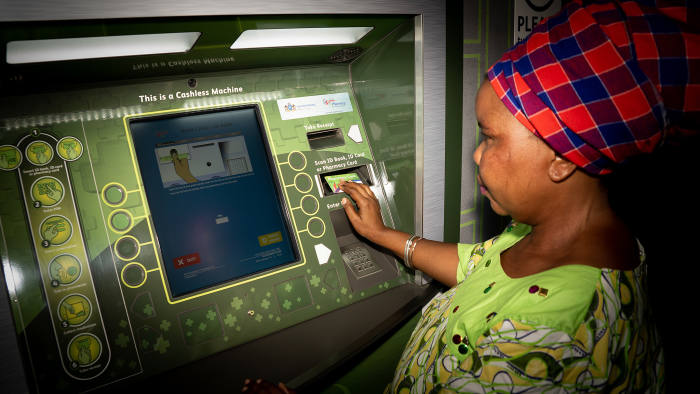 A woman at a self-service ATM-style machine at the Themba Lethu Clinic in Johannesburg PHOTO CREDIT - Bridget Corke