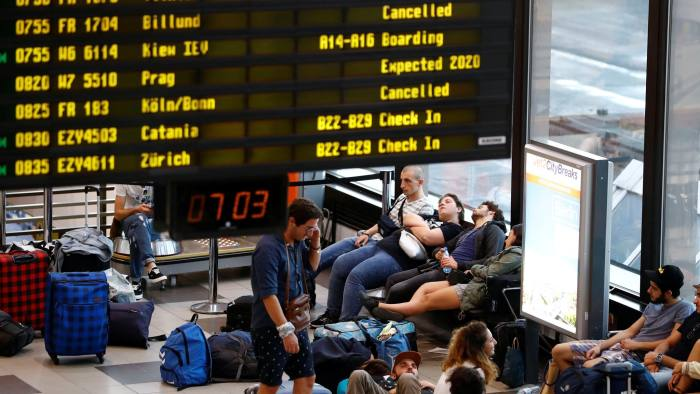 Passengers are seen at terminal A beside board showing cancelled flights during a wider European strike of Ryanair airline crews to protest slow progress in negotiating a collective labour agreement at Schoenefeld airport, south of Berlin, Germany, August 10, 2018. REUTERS/Fabrizio Bensch