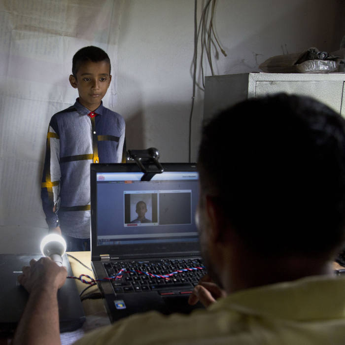 A National Register of Citizens (NRC) officer takes a photograph of a boy at an NRC center on the eve of the release of the final NRC draft in Gauhati, India, Friday, Aug. 30, 2019. India on Saturday, Aug. 31 plans to publish a controversial citizenship list that advocates say will help rectify decades of unchecked illegal immigration into the northeastern state of Assam from Bangladesh. Critics fear it will leave off millions of people, rendering them stateless. (AP Photo/Anupam Nath)
