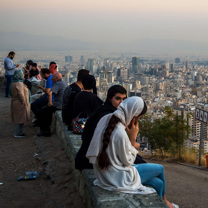 People are sitting on a stone wall at Bam-e Tehran (meaning the roof ofTehran), Iran.