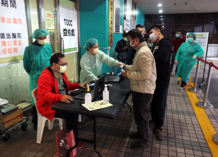 Mandatory Credit: Photo by DAVID CHANG/EPA-EFE/Shutterstock (10578808a) Medical workers, some wearing protective gowns, check people's Health Insurance Card and question their travel history, before allowing them to enter a hospital in Taipei, Taiwan, 10 March 2020. Taiwan hospitals are restricting people's entry to prevent spreading of Covid-19 coronavirus in hospital. Taiwan tightens restrictions to prevent infection of Covid-19 in hospitals, Taipei - 10 Mar 2020