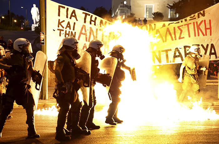 Riot police stand amongst flames from petrol bombs thrown by a small group of anti-establishment demonstrators in Athens...Riot police stand amongst the flames from exploded petrol bombs thrown by a small group of anti-establishment demonstrators in front of parliament in Athens, Greece July 15, 2015. Prime Minister Alexis Tsipras battled to win lawmakers' approval on Wednesday for a bailout deal to keep Greece in the euro, while the country's creditors, pressed by the IMF to provide massive debt relief, struggled to agree a financial lifeline. REUTERS/Yannis Behrakis TPX IMAGES OF THE DAY