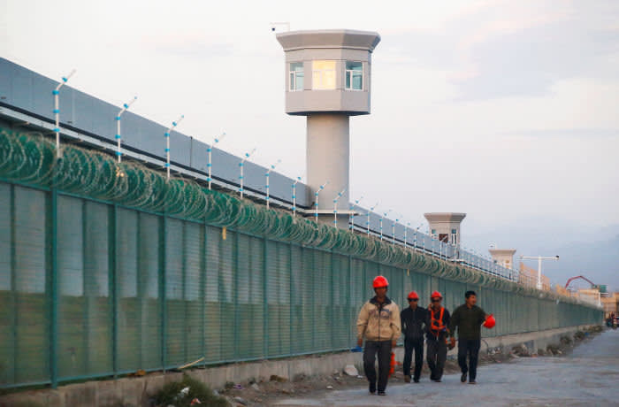 Workers walk by the perimeter fence of what is officially known as a vocational skills education centre in Dabancheng in Xinjiang Uighur Autonomous Region, China September 4, 2018. This centre, situated between regional capital Urumqi and tourist spot Turpan, is among the largest known ones, and was still undergoing extensive construction and expansion at the time the photo was taken. Picture taken September 4, 2018. To match Special Report MUSLIMS-CAMPS/CHINA REUTERS/Thomas Peter - RC11C0921B10