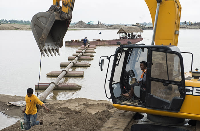 This picture taken on May 31, 2016 shows workers positioning pipes at a sand excavation site along the Mekong River in Vientiane. Grain by grain, truckload by truckload, Laos' section of the Mekong river is being dredged of sand to make cement -- a commodity being devoured by a Chinese-led building boom in the capital. But the hollowing out of the riverbed is also damaging a vital waterway that feeds hundreds of thousands of fishermen and farmers in the poverty-stricken nation. / AFP / LILLIAN SUWANRUMPHA (Photo credit should read LILLIAN SUWANRUMPHA/AFP via Getty Images)